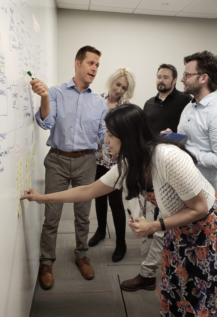 Frost leads a UX team through a design session at a whiteboard.